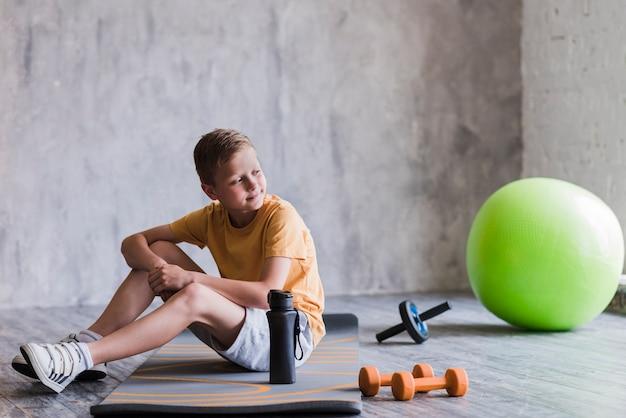 Retrato de um menino sentado perto da bola de pilates; haltere; corrediça do rolo e garrafa de água na ginástica