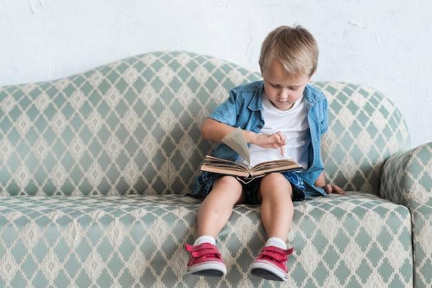 Retrato, de, um, menino sentando, ligado, sofá, apontar dedo, sobre, livro