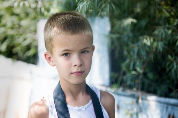 Retrato de um menino sério da criança ao ar livre.