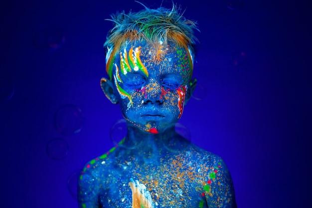 Retrato de um menino sob luz ultravioleta com bolhas de sabão