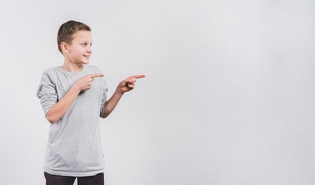 Retrato, de, um, menino sorridente, apontar dedos, em, algo, contra, fundo branco