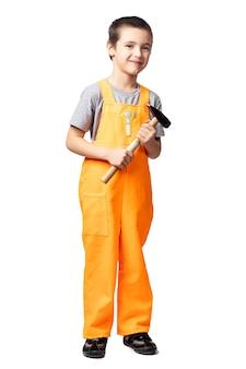 Retrato de um menino sorridente, carpinteiro com macacão laranja e segurando um martelo nas mãos
