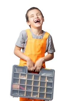 Retrato de um menino sorridente, carpinteiro de macacão laranja e segurando uma caixa de ferramentas nas mãos