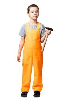 Retrato de um menino sorridente, carpinteiro de macacão laranja, posando, segurando um martelo nas mãos e se divertindo