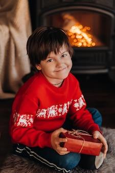 Retrato de um menino sorridente com um presente nas mãos perto da lareira em casa