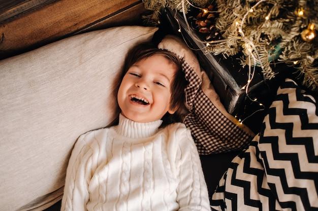 Retrato de um menino sorridente, deitado para a árvore de natal em casa.