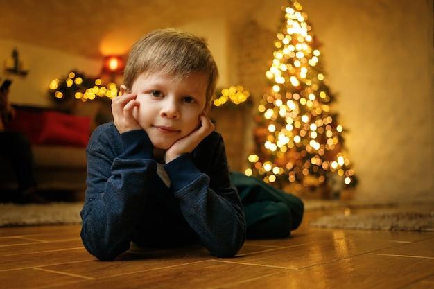 Retrato de um menino sorridente e bonito de 5 a 7 anos de idade no contexto de uma árvore de natal