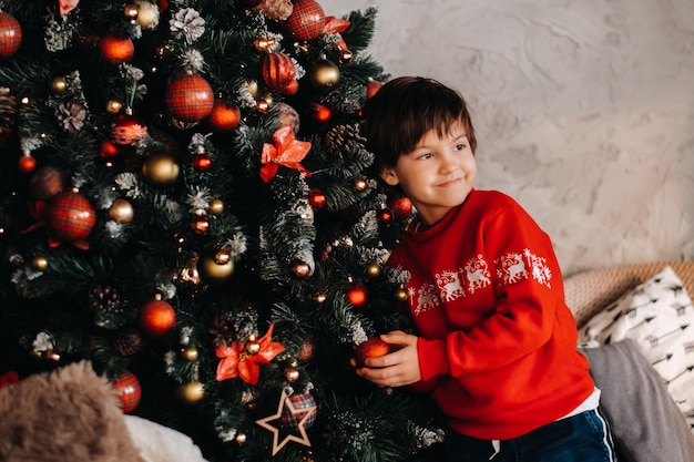 Retrato de um menino sorridente em pé na árvore de natal em casa.