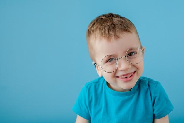 Retrato de um menino sorridente em um óculos engraçados. escola. pré escola. moda. retrato de estúdio em uma parede azul, copie o espaço
