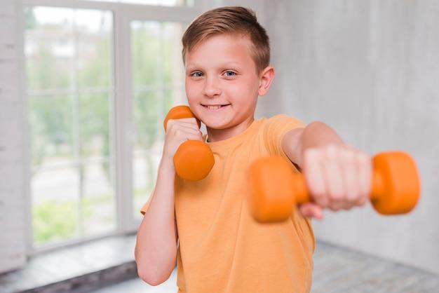 Retrato, de, um, menino sorridente, exercitar, com, dumbbell