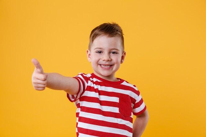 Retrato de um menino sorridente, mostrando os polegares