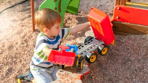 Retrato de um menino sorridente, sentado na caixa de areia do parquinho, cavando areia com uma pá de plástico e despejando-a em um caminhão de brinquedo colorido com reboque