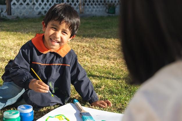 Retrato de um menino sorrindo e pintando com um pincel em uma superfície branca usando um avental