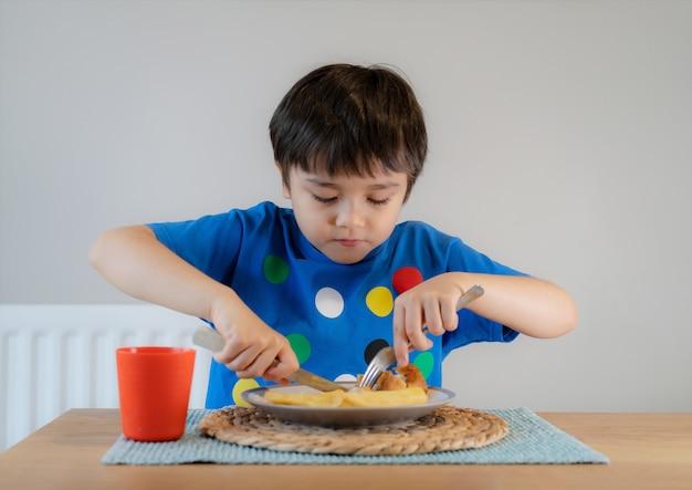 Retrato de um menino tendo peixe caseiro com batatas fritas para o jantar de domingo em casa.