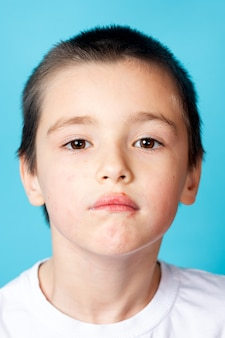 Retrato de um menino triste com dermatite perioral leve em um fundo azul
