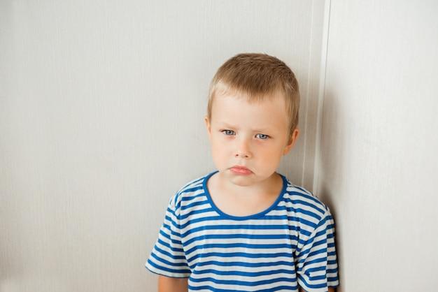 Retrato de um menino triste em pé no canto da sala, pronto para chorar
