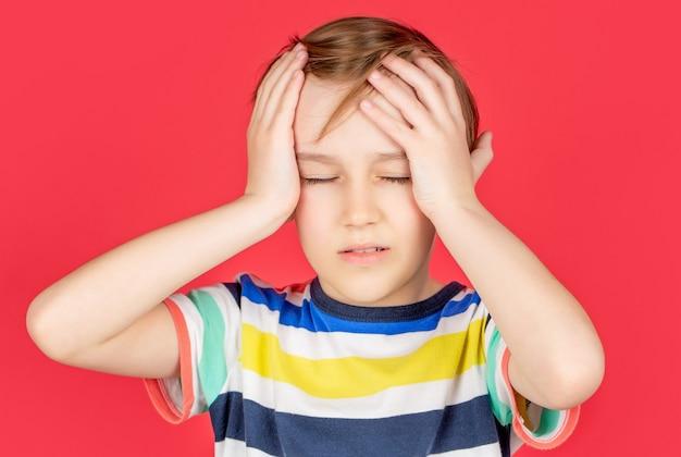 Retrato de um menino triste, segurando sua cabeça com a mão, isolada no fundo vermelho. garotinho com dor de cabeça. desespero, tragédia