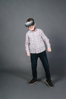 Retrato de um menino usando óculos de realidade virtual contra um fundo cinza