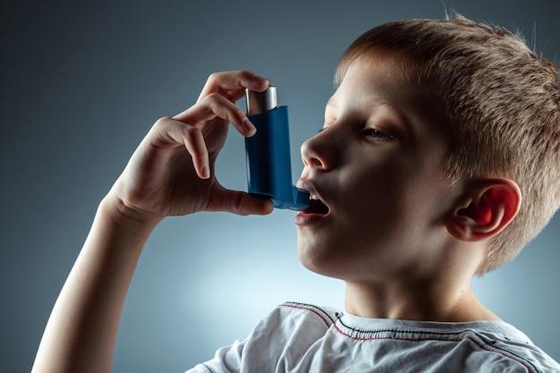 Retrato de um menino usando um inalador de asma para tratar doenças inflamatórias, falta de ar. o conceito de tratamento para tosse, alergias, doenças do trato respiratório.
