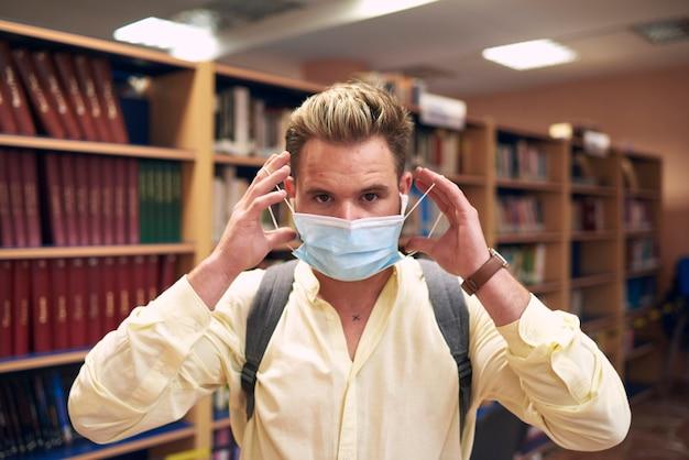 Retrato de um menino usando uma máscara para entrar na biblioteca