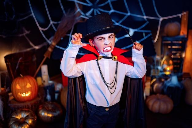 Retrato de um menino vestido com uma fantasia de vampiro e chapéu sobre fundo grunge. festa de halloween.