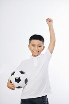 Retrato de um menino vietnamita sorridente pulando com uma bola de futebol na mão, isolado no branco