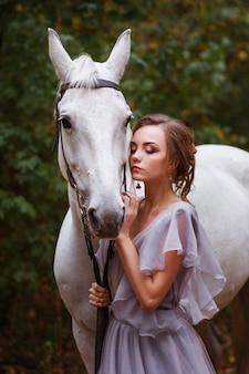 Retrato de um modelo com um cavalo branco no parque de verão. o fundo está desfocado. efeito artístico, conceito