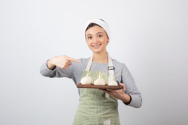 Retrato de um modelo de jovem apontando para uma placa de madeira com rabanetes brancos.