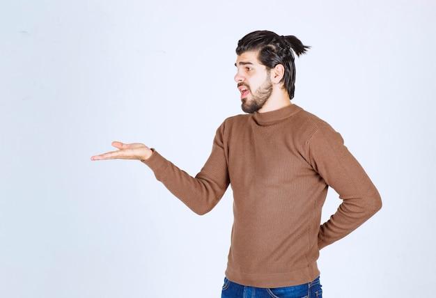 Retrato de um modelo de jovem atraente com barba mostrando a mão.