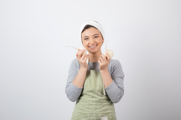 Retrato de um modelo de jovem bonito no avental segurando rabanetes brancos.