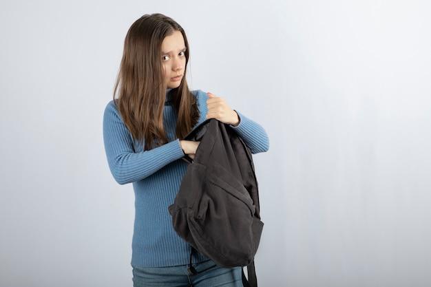 Retrato de um modelo de jovem segurando a mochila e posando.