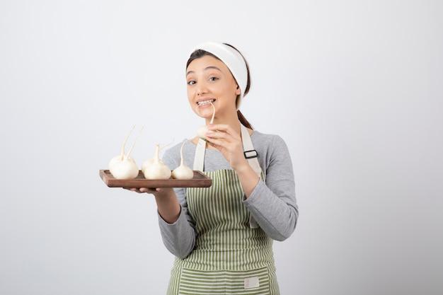 Retrato de um modelo de jovem segurando uma placa de madeira com rabanetes brancos.