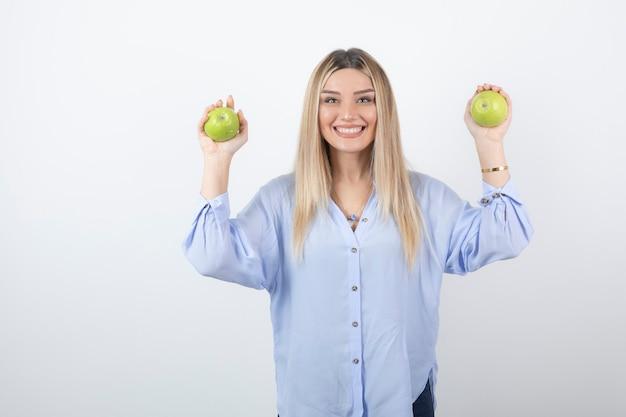 Retrato de um modelo de menina bonita em pé e segurando maçãs frescas.
