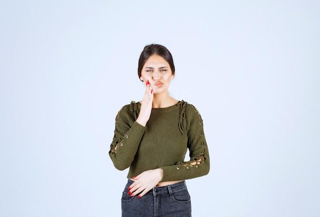 Retrato de um modelo de mulher jovem e bonita em pé e posando sobre uma parede branca.