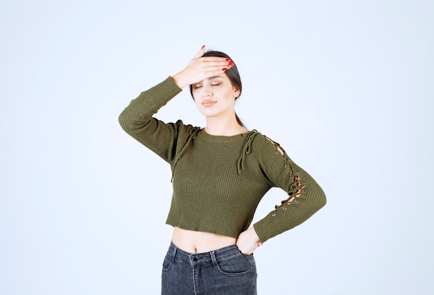 Retrato de um modelo de mulher jovem e bonita em pé e segurando a cabeça dela.