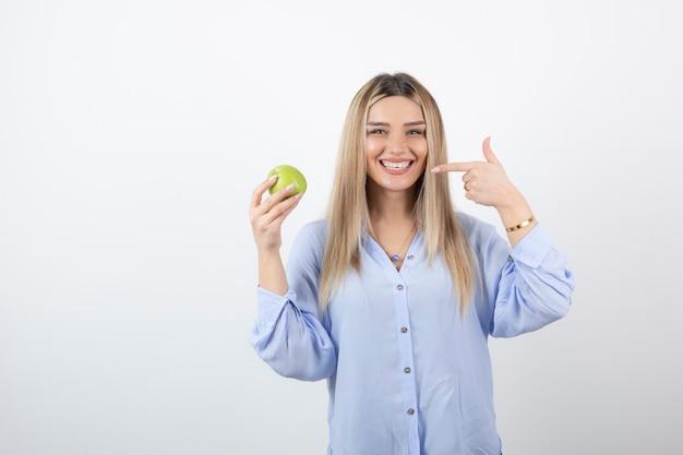 Retrato de um modelo de mulher muito atraente em pé e segurando uma maçã verde fresca.