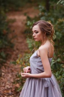 Retrato de um modelo de vestido roxo com um penteado bonito. fundo desfocado, efeito artístico.