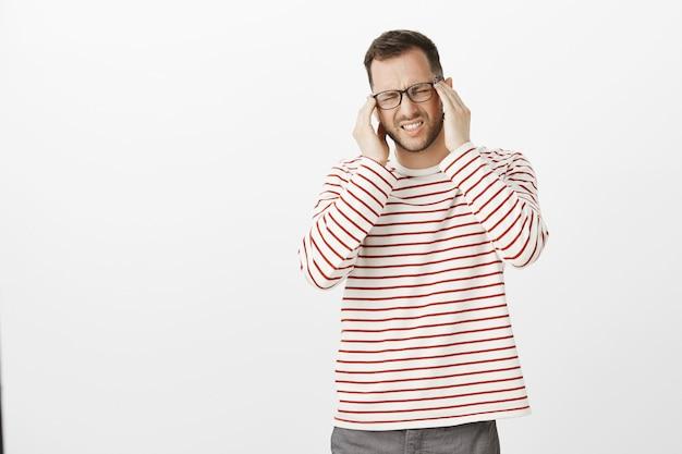 Retrato de um modelo desconfortável de homem sofrendo de óculos, fechando os olhos e fazendo careta de dor, segurando as têmporas de mãos dadas