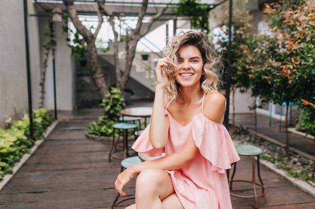 Retrato de um modelo feminino caucasiano agradável com penteado curto, sentado no café de rua. foto ao ar livre de glamourosa garota bronzeada sorrindo com plantas