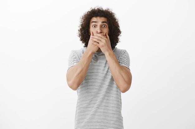 Retrato de um modelo hispânico surpreso e ansioso com penteado afro, olhando com olhos arregalados e cobrindo a boca com as palmas das mãos para não gritar, ficando chocado e assustado