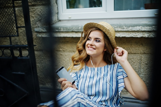 Retrato de um modelo lindo em geral listrado, sentado na cadeira ao ar livre e ouvindo música em fones de ouvido.