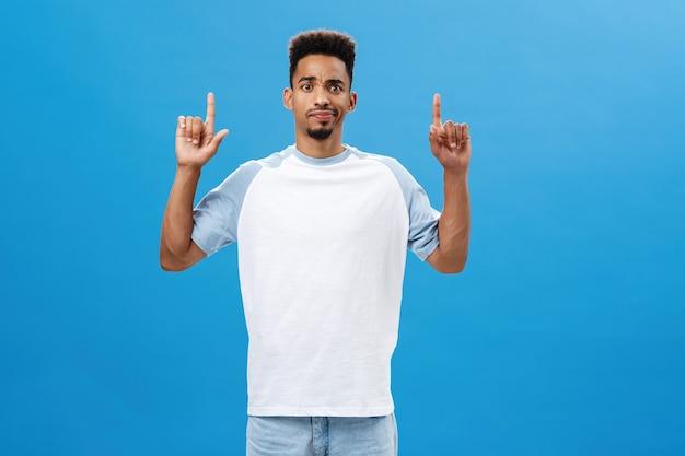 Retrato de um modelo masculino afro-americano intenso e duvidoso descontente em uma camiseta casual sorrindo e franzindo a testa de decepção e dúvida apontando para cima vendo algo suspeito sobre a parede azul