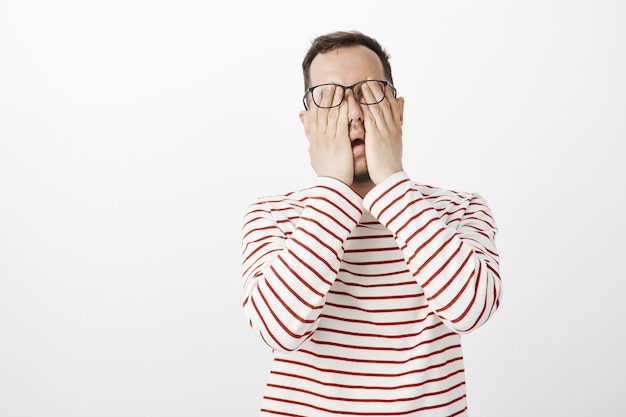 Retrato de um modelo masculino desconfortável e exausto, vestindo uma camisa listrada e óculos, esfregando os olhos, sentindo dor ou cansaço depois de ficar sentado perto do computador o dia todo