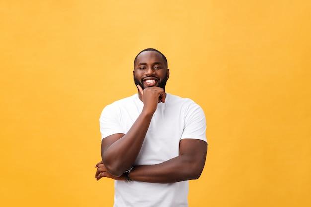 Retrato, de, um, moderno, jovem, homem preto, sorrindo, com, braços cruzaram, ligado, isolado, fundo amarelo