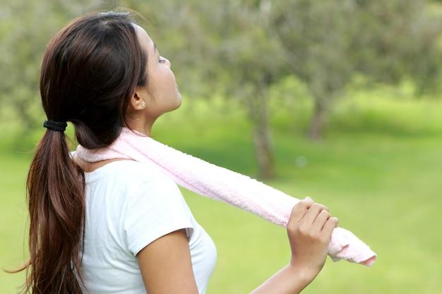 Retrato de um momento relaxado de mulher desportiva enquanto faz exercício no parque