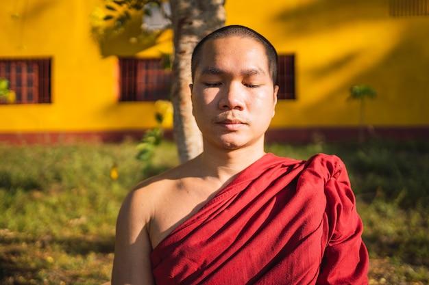 Retrato de um monge budista meditando com os olhos fechados.