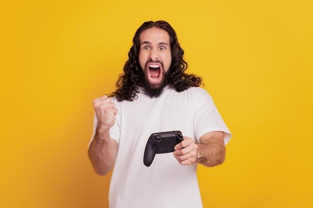 Retrato de um moreno viciado em funky segurando gamepad jogar videogame comemorar vitória em fundo amarelo