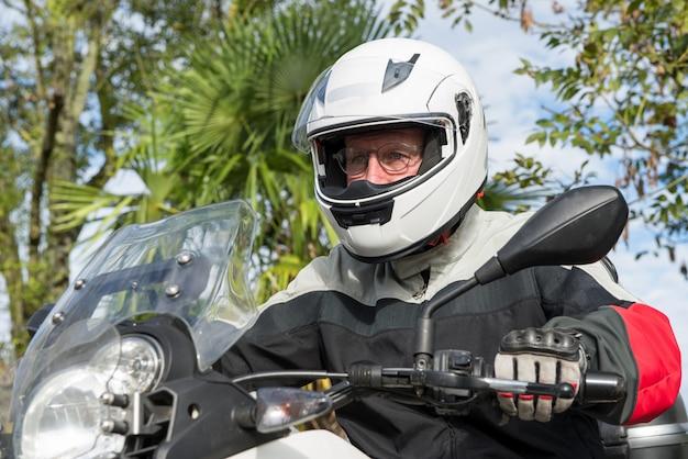 Retrato de um motociclista sênior em sua motocicleta
