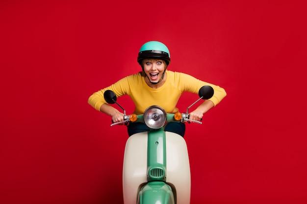 Retrato de um motociclista viciado em uma garota louca e alegre e espantada dirigindo uma bicicleta na parede vermelha