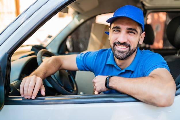 Retrato de um motorista de entregador dirigindo uma van com caixas de papelão no assento